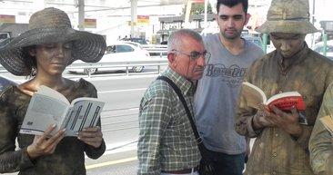 Heykel adamların metrobüste 'kitap okuma' duruşu