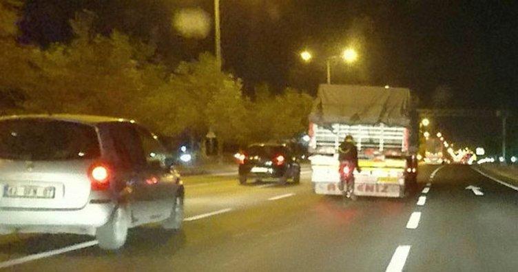 Tehlikeye aldırış etmeden bisikletiyle kamyonun arkasında seyretti